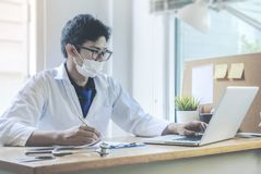 Doctor working with laptop computer and writing on paperwork. Hospital background stock photos