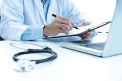 Doctor working with laptop computer and writing on paperwork. Hospital background stock images