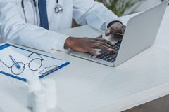 Doctor working with laptop. Cropped image of african american doctor working with laptop in clinic Stock Photography