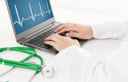 Doctor working on laptop with heart rhythm ekg on screen. Close up Royalty Free Stock Images
