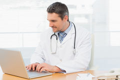 Doctor working on laptop at medical office Stock Image