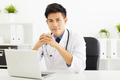 Doctor working with laptop in office Stock Images