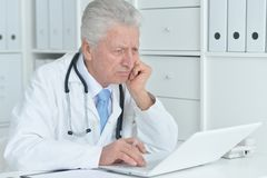 Doctor working with laptop. Senior male doctor working with laptop at his office Stock Photography
