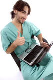 Doctor working on laptop wishing goodluck Stock Images