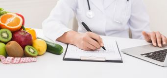Doctor working with laptop and writing on paperwork. Female doctor nutritionist working with laptop and writing on paperwork in office for medical data record royalty free stock image