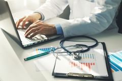 Doctor working with medical statistics and financial reports. In office royalty free stock image