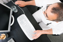 Doctor working at the PC Stock Images