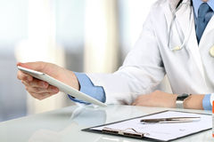 Doctor working with tablet computer.  Prescription on a table be. The Doctor working with tablet computer.  Prescription on a table behind Royalty Free Stock Photos