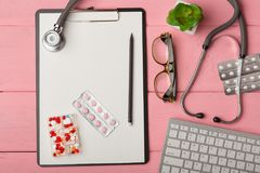 Doctor workplace with blank clipboard, medicine red stethoscope, computer keyboard, eyeglasses and pills on pink wooden table. Med royalty free stock photos