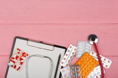 Doctor workplace with blank clipboard, medicine red stethoscope and pills on pink wooden table. Medication prescription. Health care or illness Royalty Free Stock Images