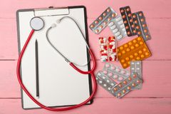 Doctor workplace with blank clipboard, medicine red stethoscope and pills on pink wooden table. Medication prescription. Health care or illness Stock Photo