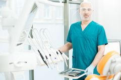 Doctor by workplace. Confident dentist in unform and protective eyeglasses looking at camera by his workplace Royalty Free Stock Photography
