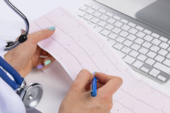 Doctor workplace. Electrocardiogram, ecg in hand of a female doctor with ekg graph paper in hospital office room with computer Stock Images
