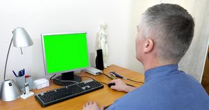 Doctor works at a computer with a green screen
