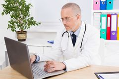 Doctor works at the computer in his office in clinic royalty free stock image