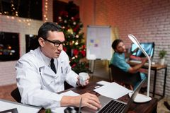 The doctor works on New Year`s Eve. He communicates with a colleague who shows him an X-ray photograph. Behind him works a colleague. Against the backdrop of a royalty free stock photo