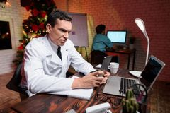 The doctor works on New Year`s Eve. He looks at something on the tablet. Behind him works a colleague. Against the backdrop of a Christmas tree Stock Photo