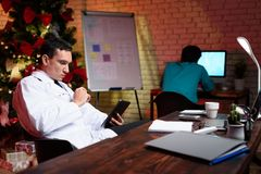 The doctor works on New Year`s Eve. He looks at something on the tablet. Behind him works a colleague. Against the backdrop of a Christmas tree Royalty Free Stock Photos