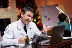The doctor works on New Year`s Eve. He is talking to someone on video. Behind him works a colleague. Stock Photography