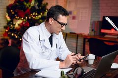 The doctor works on New Year`s Eve. He is very tired but continues to work. Stock Photos