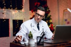 The doctor works on New Year`s Eve. He is very tired but continues to work. Royalty Free Stock Image