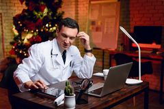 The doctor works on New Year`s Eve. He is very tired but continues to work. Stock Photo
