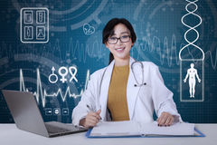 Doctor works with virtual screen background. Beautiful female doctor working with a laptop and document on desk, shot with virtual screen background Stock Images