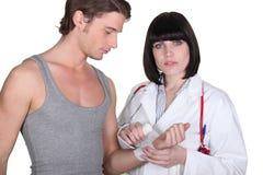 Doctor wrapping gauze around wrist. Doctor wrapping gauze around a patient's wrist Royalty Free Stock Photo