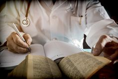 Doctor writes on a book of ancient medicine Royalty Free Stock Images