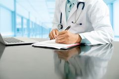Doctor writes on documents at hospital office. Male doctor sitting at table and writing on a document report in hospital office. Medical healthcare staff and royalty free stock photography