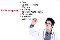 Doctor writes Ebola symptoms Stock Photos