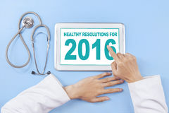 Doctor writes healthy resolution for 2016 on tablet Stock Images