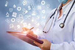 Doctor writes information to the history of the disease . Royalty Free Stock Photo