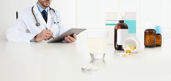Doctor writes the medical prescription with the digital tablet on a desk office with glass, aspirin and drugs, cold and flu cure. Concept, web banner and white stock images