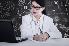 Doctor writes medical reports Stock Images