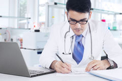 Doctor writes medicine recipe in the lab Stock Images