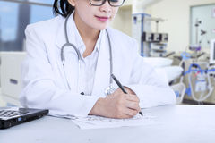 Doctor Writes A Note. Female doctor writing a note while using laptop at the hospital Stock Photography