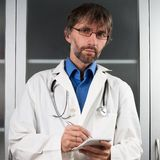 Doctor writes in a notebook. To the clinic Royalty Free Stock Photography