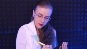 Doctor writes on paper. Beautiful girl doctor writes on paper, pen sounds. Reception of the patient in the clinic stock footage