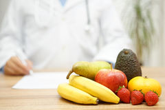 Doctor writes the prescription for diet Royalty Free Stock Image