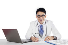 Doctor writes a prescription and looking at camera Royalty Free Stock Image