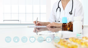 Doctor writes the prescription in medical office with drugs Royalty Free Stock Photos