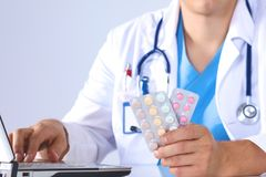 The doctor writes a prescription pill on the computer.  Stock Photo