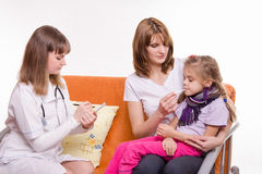 Doctor writes a prescription for sick girl who sits at mum on hands Royalty Free Stock Photography