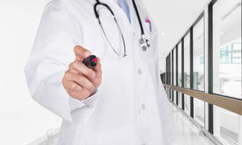 Doctor writing on the air with marker in hospital hallway.  royalty free stock image