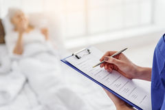 Doctor writing answers of grandmother in hospital Royalty Free Stock Photos