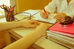 Doctor Writing application form while consulting patient. Medical and Health care concept Royalty Free Stock Images