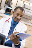 A Doctor Writing On A Clipboard Royalty Free Stock Images
