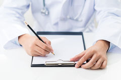 Doctor writing. On a clipboard Royalty Free Stock Photo