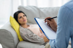 Doctor writing on clipboard while consulting pregnant woman. Doctor writing on clipboard while consulting pregnant women at home Royalty Free Stock Image